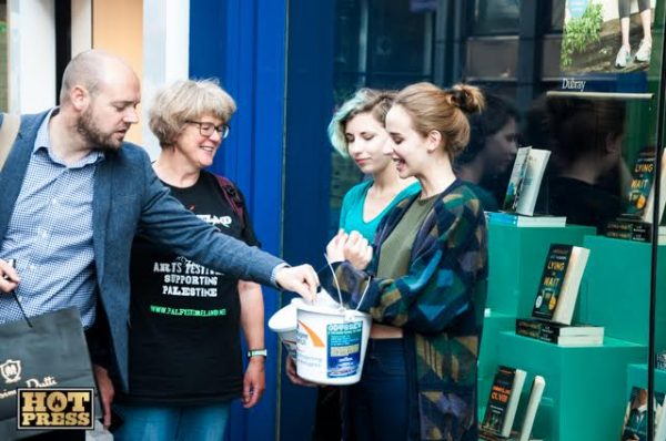 Laura Doak and Anna Wardell  collecting money  at nine-hour continuous reading of the Odyssey to Fundraise for Calais Refugees, Dubray Books, Grafton Street.